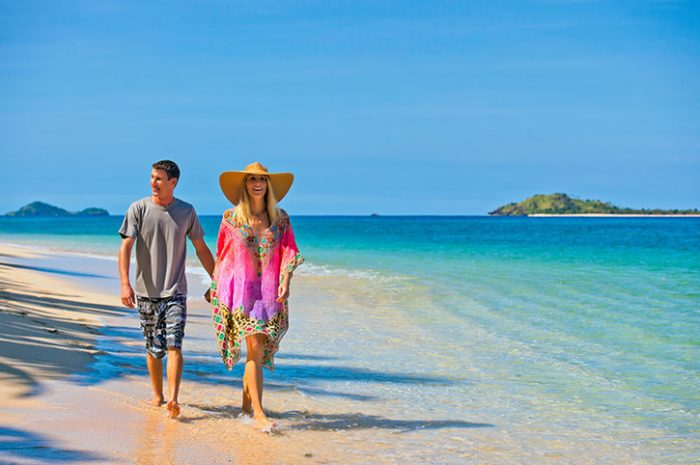 Couple Strolling Along A Fijian Beach