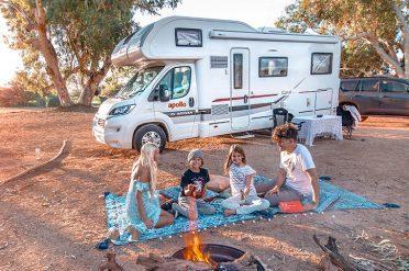 Family enjoying a picnic beside motorhome