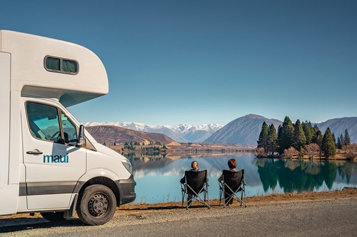 Couple sitting in front of lake in New Zealand with Maui 6 Berth motorhome by their side