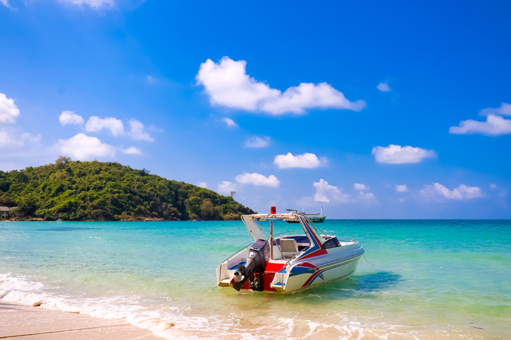 Motor-boat-at-the-water's-edge-on-Koh-Samet-beach,Thailand